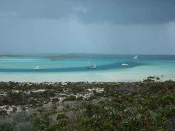 "Dragonsbane anchored in the lagoon ""the boat in blue"" with a squall in the background"