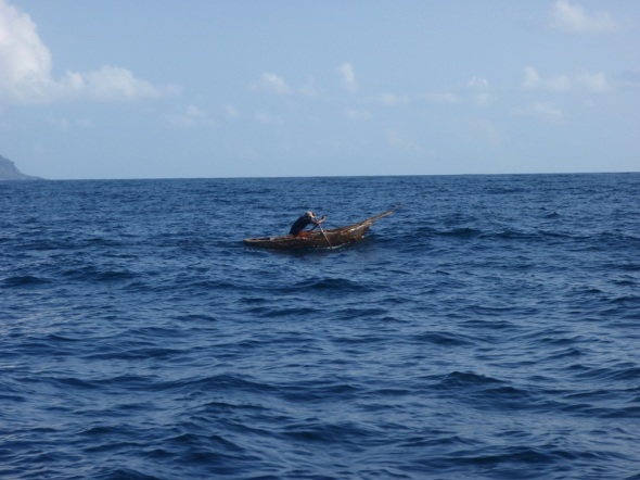 A Man trolling for fish out on the ocean